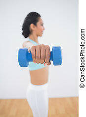 Sporty young woman lifting blue dumbbells standing in...