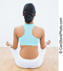 Rear view of slender calm woman meditating in lotus position...