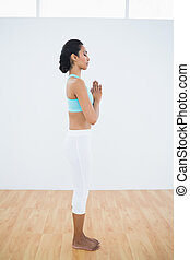 Calm relaxed woman standing in fitness hall with hands in...
