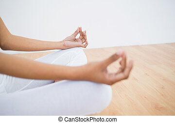 Mid section of slender young woman meditating sitting in...