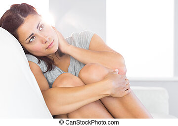 Melancholic gorgeous woman sitting on her couch in the...