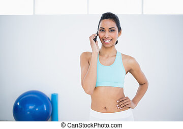 Gleeful sporty woman phoning while standing in fitness hall...