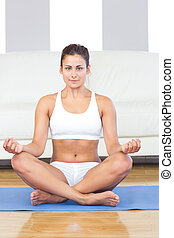 Pretty sporty woman in sportswear sitting on an exercise mat in her living room in lotus position