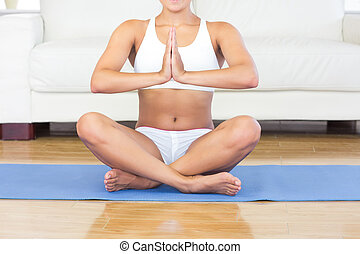 Mid section of young woman sitting in lotus position on an exercise mat in her living room