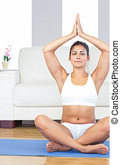 Gorgeous young woman sitting in lotus position on a blue exercise mat in her living room at home