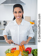 Lovely smiling woman cutting vegetables smiling at camera