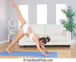Sporty woman stretching her body with yoga pose on an exercise mat in her living room