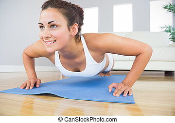 Young fit woman doing press ups on an exercise mat in her...