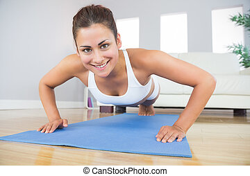 Portrait of fit woman practicing press ups in her living...