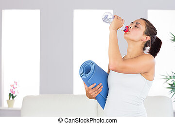 Attractive woman drinking out of a bottle while holding an exercise mat in her living room
