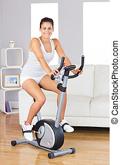Cheerful young woman training on an exercise bike in her living room smiling at camera