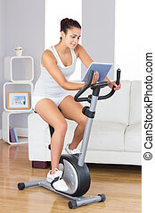 Content slim woman using her tablet while training on an exercises