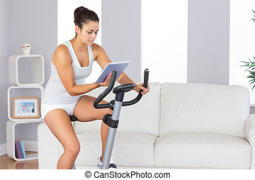 Concentrated slender woman training on an exercise bike while using her tablet in her living room