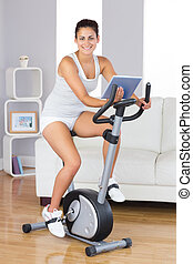 Happy training woman using an exercise bike while holding a tablet in her living room