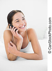 Smiling woman using mobile phone in bed