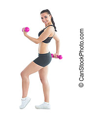 Side view of smiling active woman training with dumbbells...