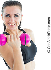 Joyful attractive woman smiling at camera while training with a dumb-bell on white background