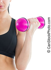 Mid section of slender active woman training her arm with a...