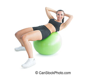 Joyful fit woman doing an exercise on an exercise ball...