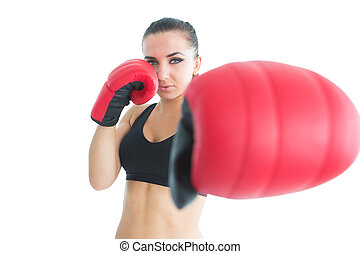 Sporty young woman posing wearing boxing gloves looking at...