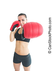 Attractive cheerful woman wearing red boxing gloves on white...