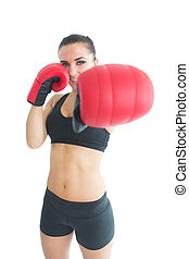 Beautiful sporty woman posing wearing red boxing gloves...