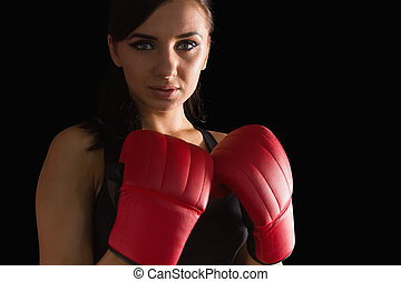 Beautiful sporty woman wearing boxing gloves looking at...