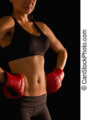 Mid section of young sporty woman posing and wearing boxing...