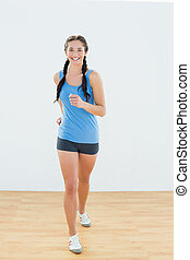 Portrait of a sporty woman in jogging posture at fitness...