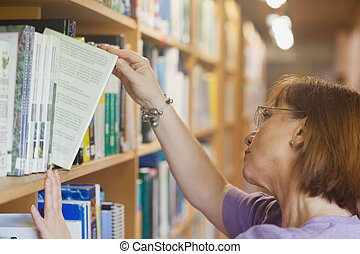 Mature female librarian searching a book in library
