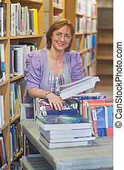 Content calm female librarian returning books smiling at...
