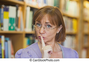 Mature female librarian giving a sign to be quiet standing...
