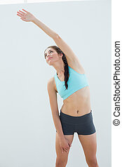 Sporty young woman stretching hand over white background