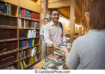 Mature female librarian handing a book to young man in...