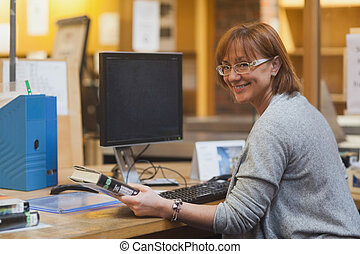Smiling female librarian holding a book standing behind the...