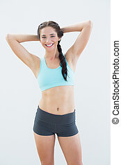Fit smiling woman standing with hands behind head - Portrait...