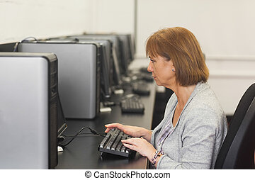 Concentrated female mature student sitting in computer class...