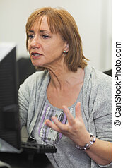 Irritated mature woman working on computer sitting in...