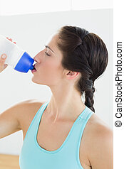 Close-up of a fit woman drinking water at the gym