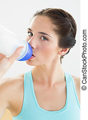 Close-up of a woman drinking water at the gym