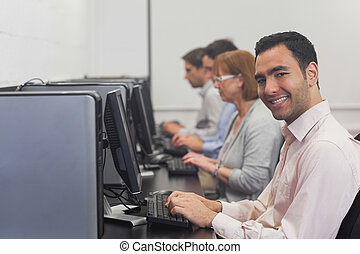 Cheerful mature student sitting in computer class smiling at...
