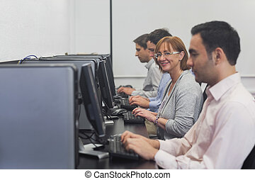 Happy female mature student sitting in computer class...