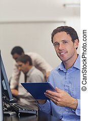Content male student holding his tablet sitting in computer class smiling at camera