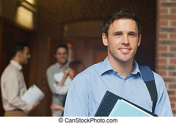 Mature male student posing in corridor smiling at camera