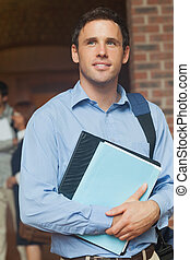 Handsome male mature student posing holding some files in...