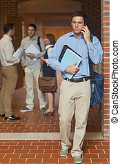 Attractive mature student phoning with his smartphone...