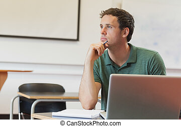 Thoughtful handsome mature student sitting in classroom...
