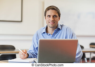 Handsome mature student learning and sitting in classroom...