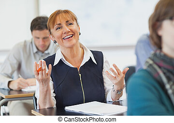 Laughing female mature woman sitting in classroom talking to...