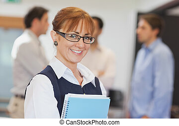 Portrait of female mature student posing in classroom...